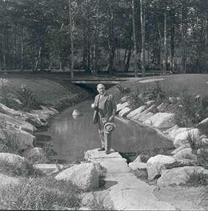 US Representative William Bourke Cochran holds a cup of spring water in front of the Sieur de Monts Spring Pool, ca. 1917.