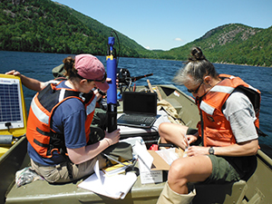 Dr. Courtney Wigdahl (left) and ANP employees Alyssa Reischauer (right) and Bill Gawley (hiding behind) prepare to launch the new water-quality measurement buoy in Jordan Pond.