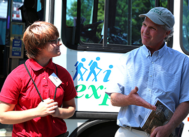 Marisa Gray receives congratulations from Friends of Acadia president David MacDonald, on being the 5-millionth rider of the Island Explorer bus system.