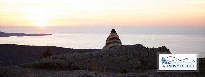 A park visitor watches sunrise from Cadillac Mountain.
