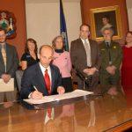 Then-Governonr John Baldacci signs legislation that will help protect Acadia's environment